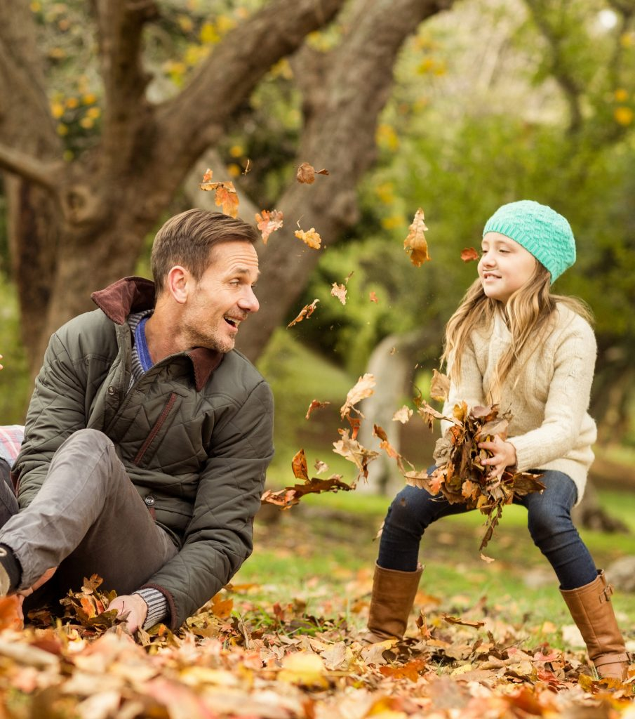 Dad and daughter playing together in fall leaves