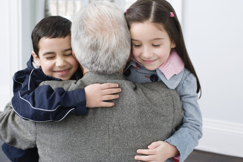Kids hugging thier grandpa