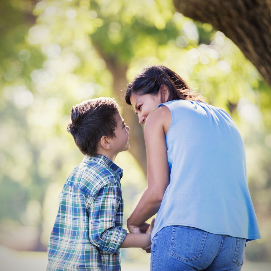 Loving mom talks sweetly to son outside