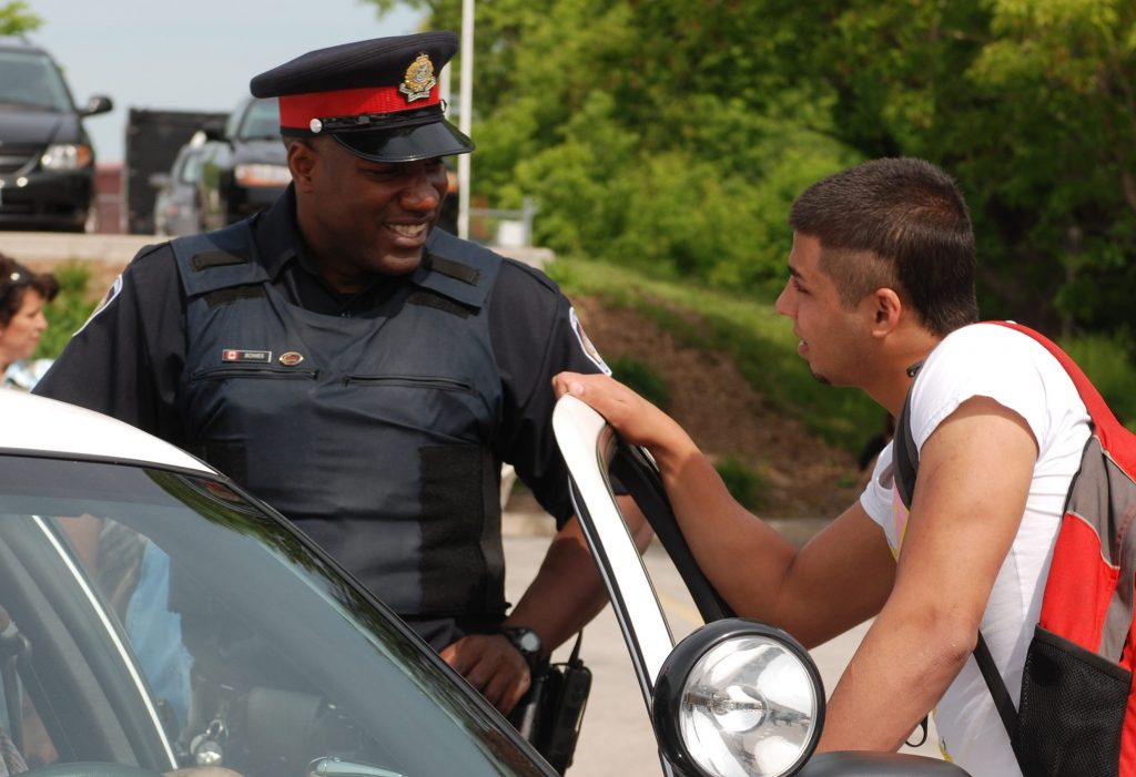 Police constable talking and laughbing with teenager.