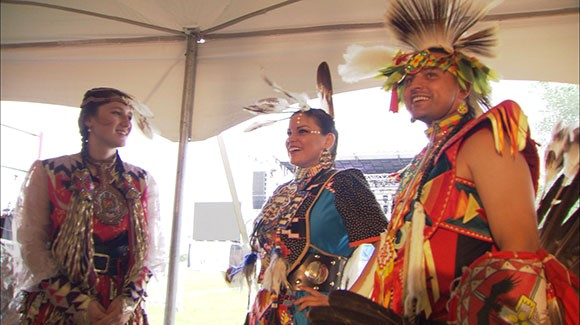 Three Indigenous people in traditional dress are smiling and talking