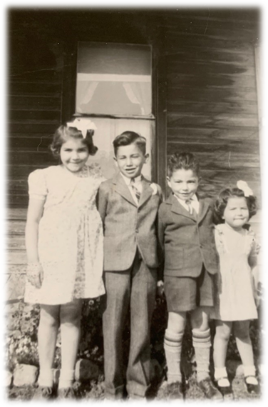 Four Indigenous children stand in front of a house. They are all dressed in new formal suits and dresses.